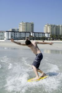 Teenage boy skimboarding
